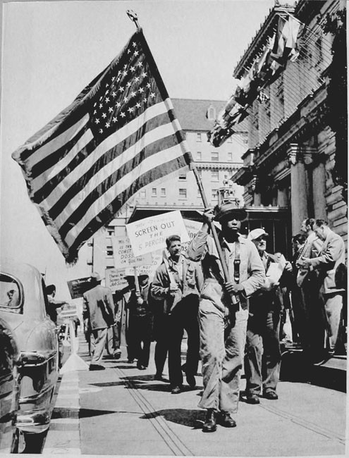 Longshoreman and other waterfront workers picket in front of the